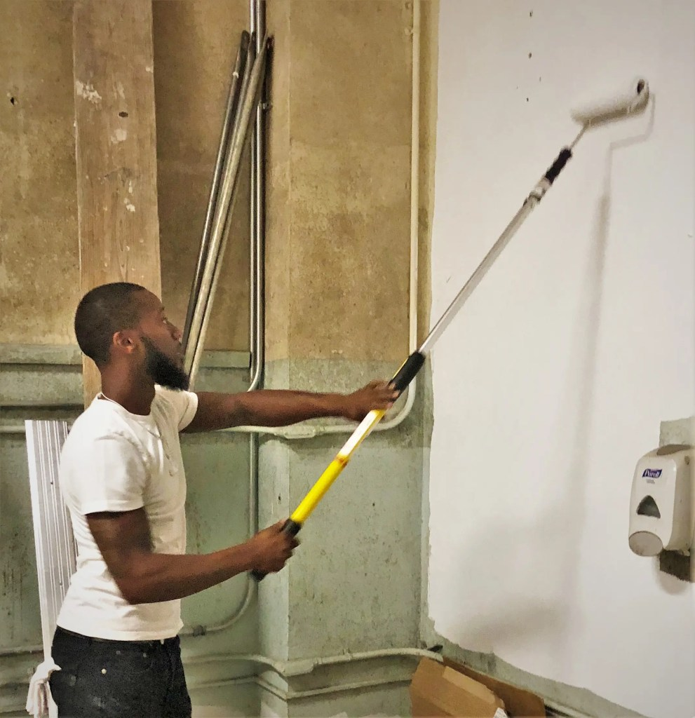 Hard at work on a Rebuild project to renovate a local recreation center, Rebuild pre-apprenticeship trainee Allen Wood applies paint on a basement wall.