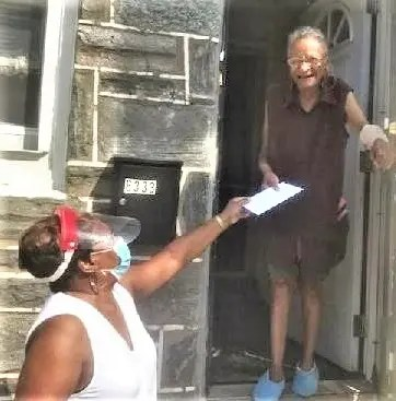 Lorraine Thomas (left) drops off a Walmart electric fan gift card for a sweltering Southwest Philadelphia senior. Thomas delivered 60 cards funded by generous donations of Wayne Presby. CityLights.