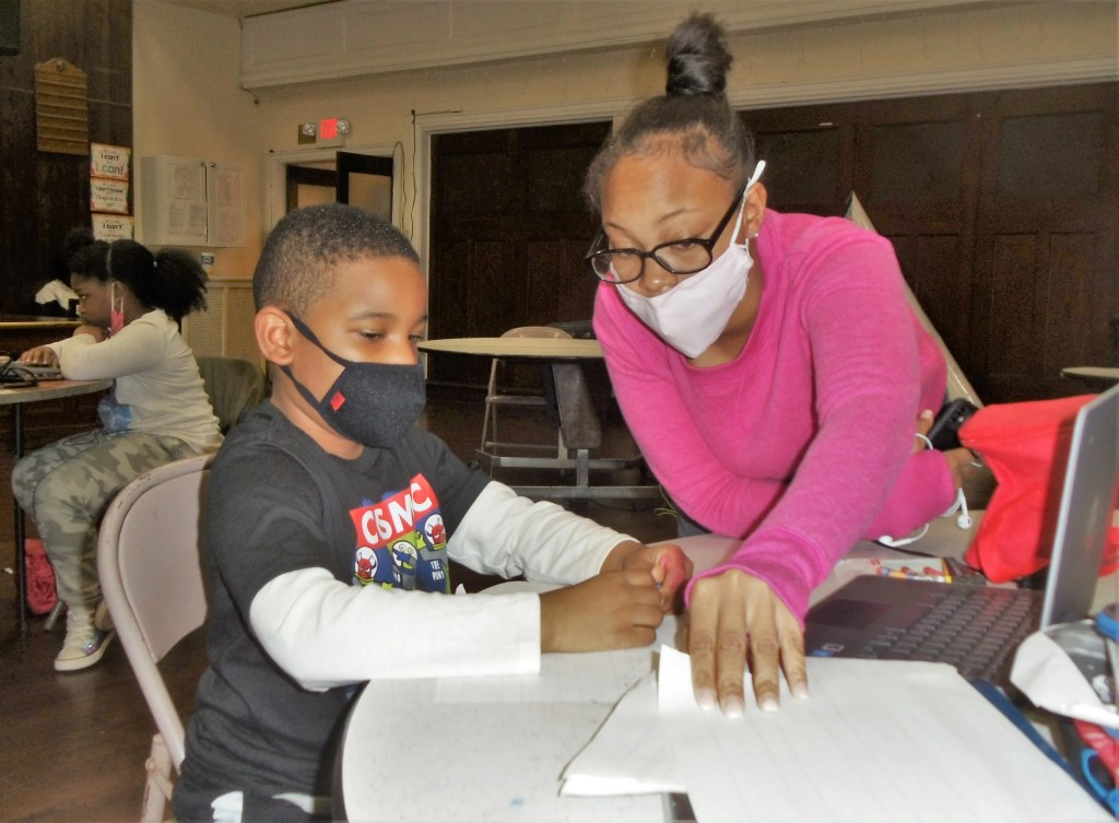 A staff member of The Common Place provides homework help to a youngster during the current pandemic crisis