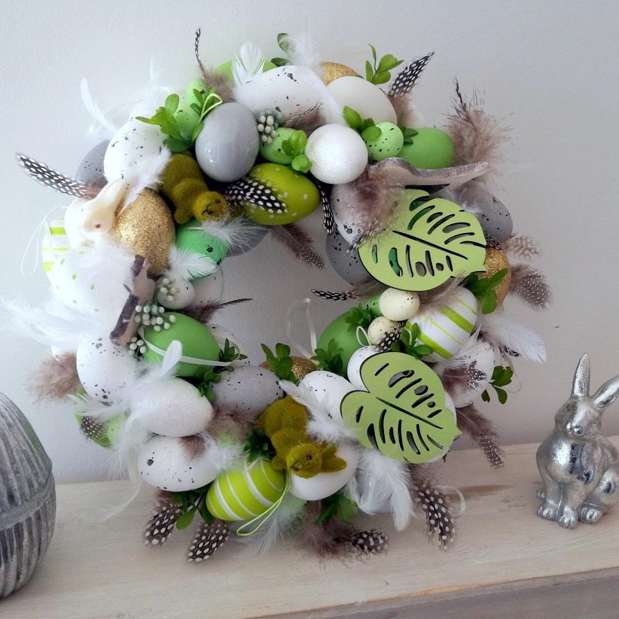Wianek Wielkanocny biało zielony nr 127 Wianek Wielkanocny biało zielony nr 127 to śliczna dekoracja wielkanocna. Wianek wykonany z ogromną starannością i dbałością o szczegóły. Ozdobiony został welurowymi króliczkami, drewnianymi zajączkami, wielokolorowymi pisankami, listkami bukszpanu oraz pięknymi piórkami. Piękna kolorystyka, nowoczesny disign czyni z dekoracji niezastąpiony element dekoracyjny wiosennego stołu. Wianek może stanowić wspaniały prezent. Pięknie będzie się prezentować zarówno jako dekoracja świątecznego stołu, komody czy też stołu. Wianek wykonany został na słomianym podkładzie. Wymiary wieńca Średnica 32-33 cm