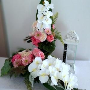 estaw nagrobny odcienie różu i bieli nr 346 Zestaw nagrobny odcienie różu i bieli nr 346 jest to elegancka kompozycja przeznaczona na cmentarz. Elementy zielone zastosowane w tej kompozycji nagrobnej to: paproć, liście bananowca oraz liście monstery, uzupełnione kwiatami róży oraz gerbery. Trzon dekoracji to piękne, białe storczyki. Prosta forma nadaje kompozycji lekkości i elegancji. Storczyki i gerbery pięknie ze sobą współgrają tworząc harmonijną całość. Stroik osadzony w plastikowej, obciążonej donicy w kształcie łódeczki praktycznie na każdym nagrobku będzie się prezentować pięknie ze względu na swoją okazałą formę oraz kolorystykę. Bukiet osadzony jest w plastikowym wkładzie. Wszystkie kwiaty wykorzystane w kompozycji to dobrej jakości sztuczne kwiaty. Nie ma dwóch takich samych