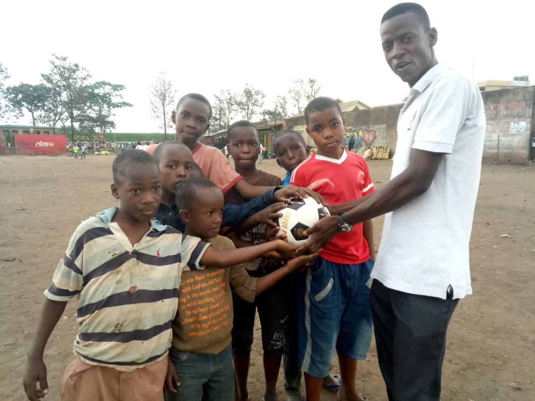 John Nanyumba handing over the ball to the kids
