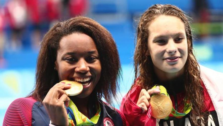 Aug 11, 2016; Rio de Janeiro, Brazil; Simone Manuel (USA) and Penny Oleksiak (CAN) with their gold medals after the women's 100m freestyle final in the Rio 2016 Summer Olympic Games at Olympic Aquatics Stadium. Mandatory Credit: Rob Schumacher-USA TODAY Sports