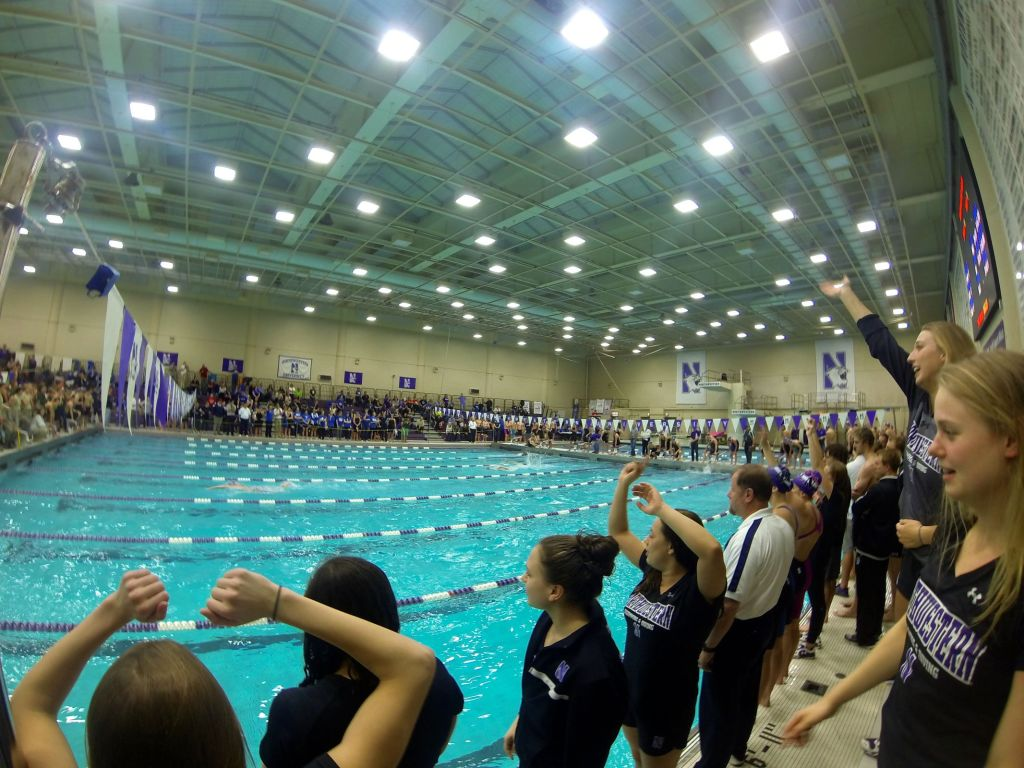 Northwestern team members anxiously watch their A- 400 free relay as they attack the pool record.