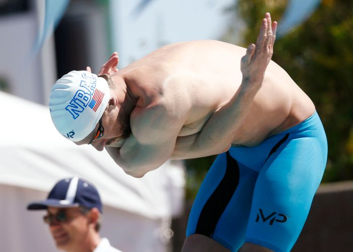 Apr 16, 2015; Mesa, AZ, USA; Michael Phelps stretches on the block in the Men's 100 meter butterfly prelims during the 2015 Arena Pro Swim Series at the Skyline Aquatic Center. Mandatory Credit: Rob Schumacher/Arizona Republic via USA TODAY Sports