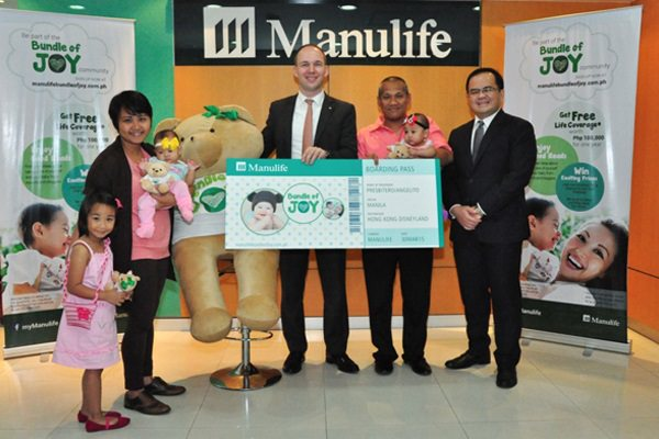 Manulife Philippines President and Chief Executive Officer Ryan Charland (center) and Manulife Philippines Senior Vice President and Alternative Distribution Head Anthony Perez (far right) present  the Presbitero family, winners of a lucky draw with  a trip to Hong Kong Disneyland.