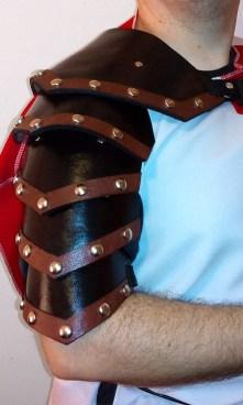 Ombreira (pauldron) segmentada de couro rebitado