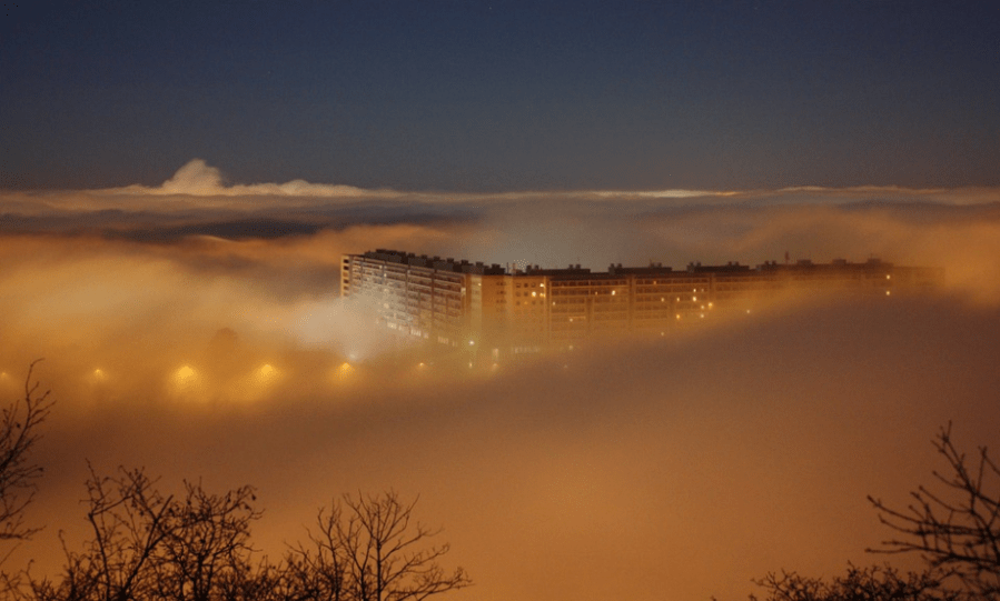 a condo building covered by night mist