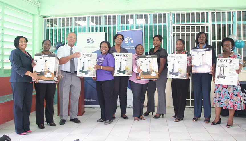 SXM Managing Director, Regina LaBega (first from left) and Acting Chairman of the Supervisory Board of Directors, Cleavland Beresford (3rd from left) join the school managers and Head of Public Education, Mrs. Glenderlin Davis-Holiday (2nd from right) in posing with the milk/tea dispensers presented to the public schools Friday. (SXM Airport photo)
