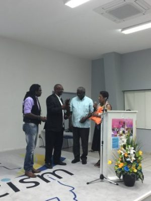 Dr. Quince Duncan (2nd r) is about to receive the Presidents Award of the St. Martin Book Fair 2016 from book fair coordinator Shujah Reiph, while Mrs. Jacqueline Sample (r), president of House of Nehesi Publishers, explains that the ebony statue was made in Nigeria. Looking on is Dr. Francio Guadeloupe, president of the University of St. Martin. (Photo courtesy: C. Davis-Kahina)