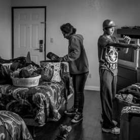 """While Melissa A. Ramon unpacks their belongings, her 13-year-old son Sam plays with a toy gun in their room at a motel In Pomona, CA that they call """"The Jungle."""" They vacated the previous motel (that charged $37.50 for two hours), because a male stranger masturbated in front of her in the laundry room. ©Calvert"""