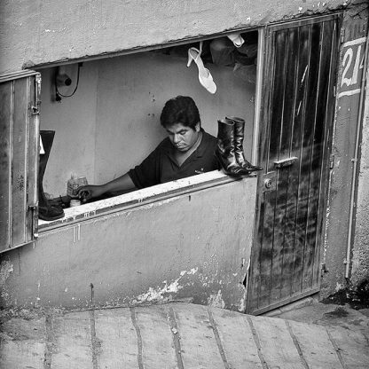 El Zapatero ©Owen Murphy I was passing by in a bus seated by the window when this humble cobbler's shop came into view. His solitude was magnified by that single white shoe.