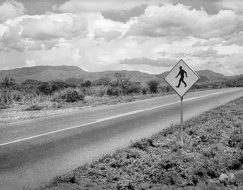 The Traveler ©Owen Murphy Along the coastal highway, the pedestrian sign was a reminder to drivers to be aware of sharing the road. It became a metaphor for me, the solitary traveler(el viajero) alone in the middle of nowhere.