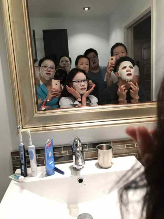 A group of 8 people crammed in a bathroom putting facial sheet masks on after a day of exploring the city.