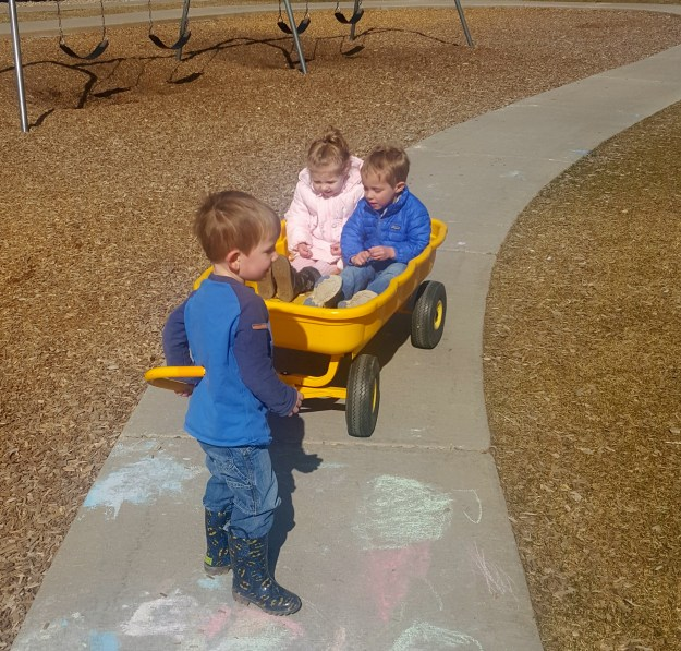 In the playground, at school, Bo pulled Sydney and Tennyson around in the wagon. (3/1/16)