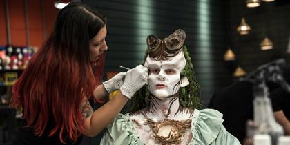contestant applies makeup to an alien face