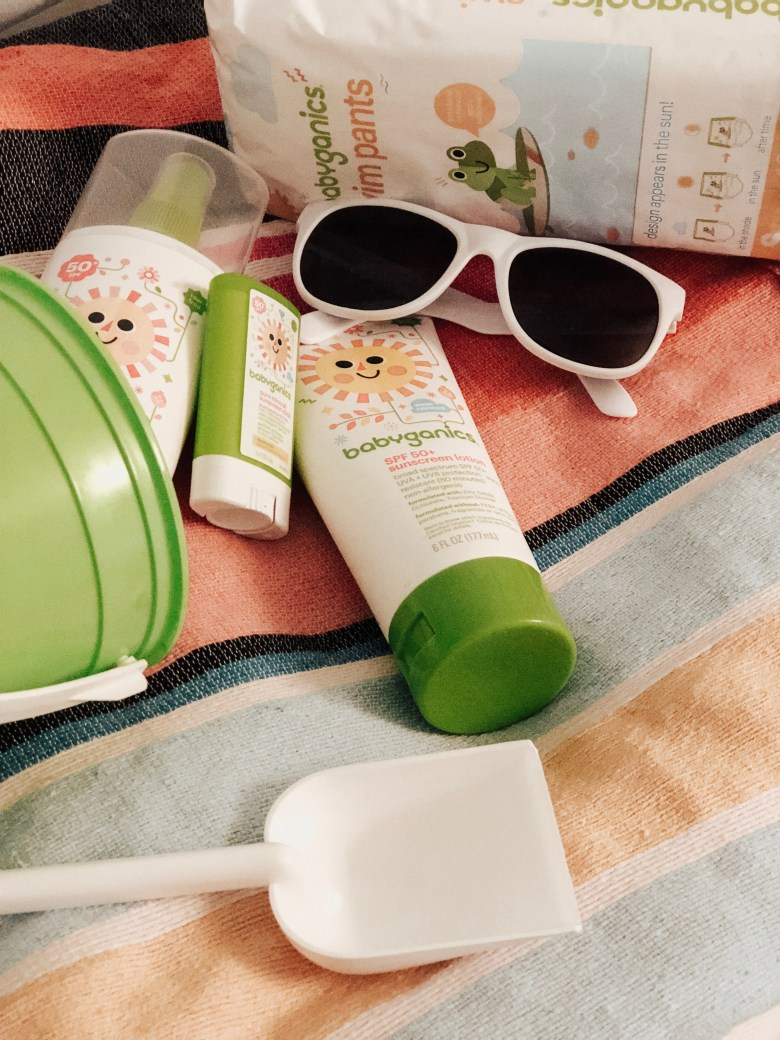 BABY SUN SAFETY featured by top US mommy blogger Sylvie In The Sky | Babyganics by popular San Francisco motherhood blog, Sylvie in the Sky: image of Babyganics sunscreen products next to a green sand bucket and pair of white frame sunglasses.