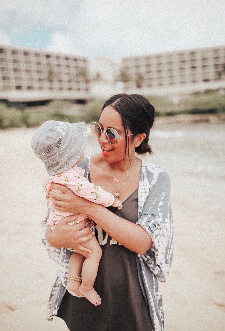 BABY SUN SAFETY featured by top US mommy blogger Sylvie In The Sky | Babyganics by popular San Francisco motherhood blog, Sylvie in the Sky: image of a mom holding her baby on the beach.