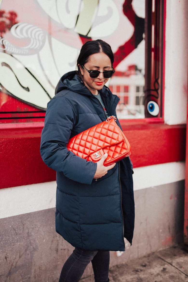STYLE: THE BEST AFFORDABLE WINTER COATS UNDER $100 FOR WOMEN featured by top San Francisco fashion blogger Sylvie in the Sky | STYLE: THE BEST AFFORDABLE WINTER COATS UNDER $100 FOR WOMEN by popular San Francisco fashion blog, Sylvie in the Sky: image of a woman standing outside and wearing a navy puffer coat and holding a quilted red Chanel purse.