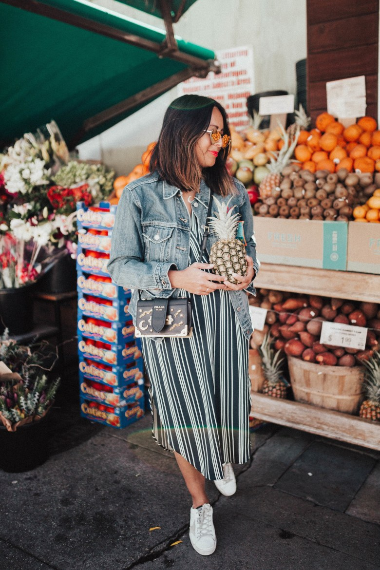 Health Benefits of Eating Pineapple featured by top US lifestyle blogger Sylvie in the Sky; Image of a woman holding a pineapple.