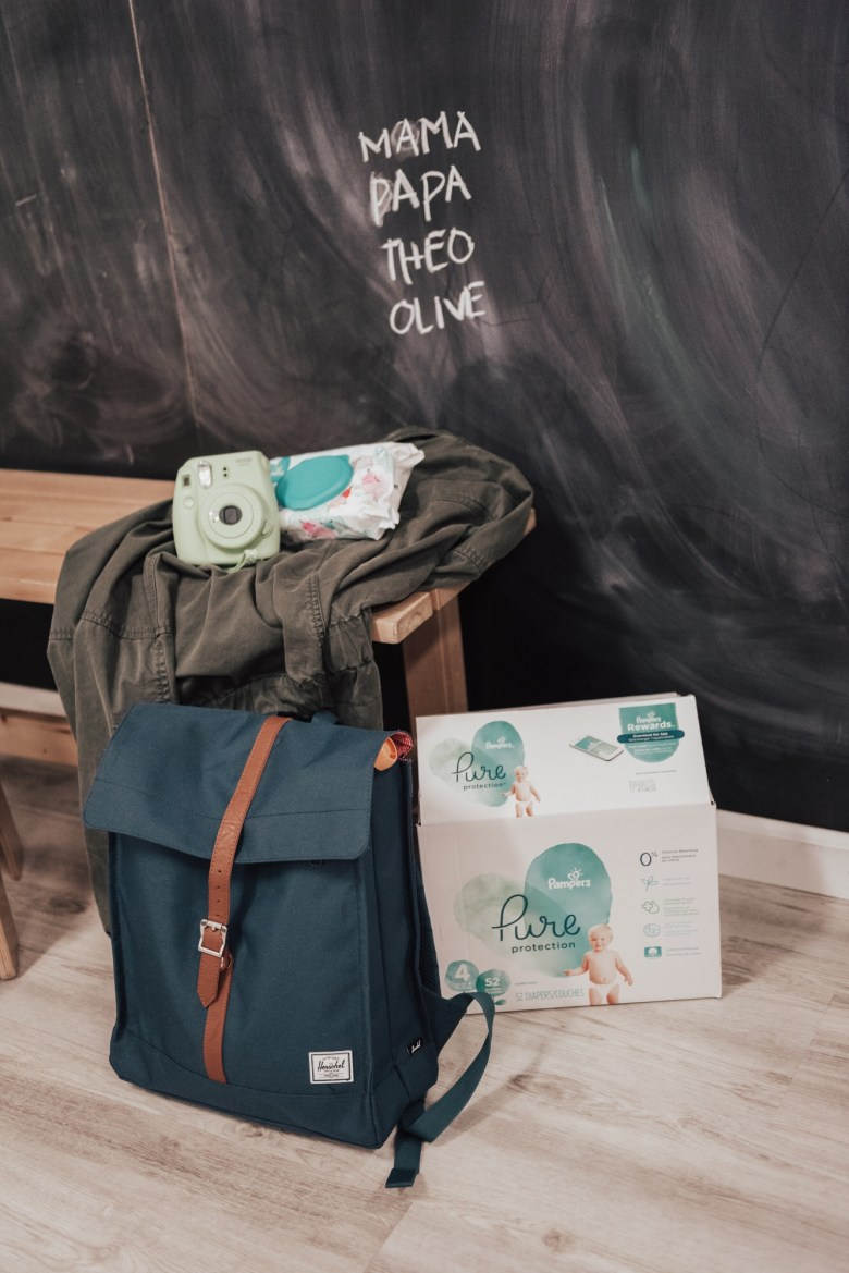 14 Amazing Activities for Dads and Kids by top US lifestyle blog, Sylvie in the Skye: image of chalkboard with writing on it, and a wooden bench with a polaroid instax camera, pampers diaper wipes, green jacket, blue diaper bag, and box of Pampers Pure Protection diapers on it.