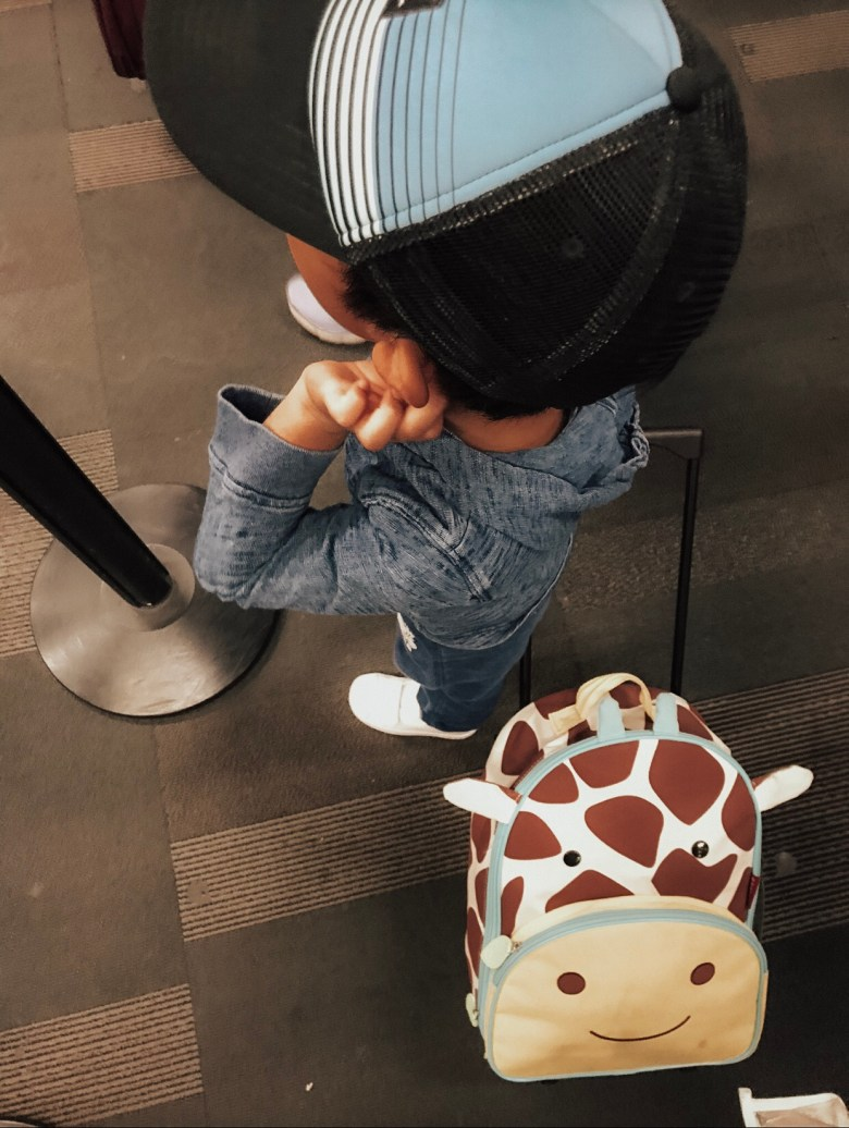 GO: LABOR DAY TRAVEL WITH KIDS by popular San Francisco travel blog, Sylvie in the Sky: graphic image of a little boy standing in an airport terminal and holding his giraffe luggage behind him.
