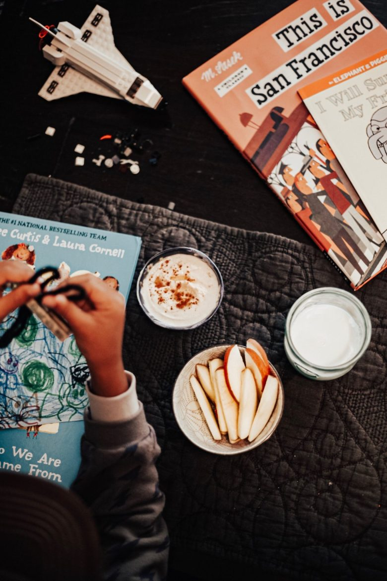 Healthy After School Snacks: Peanut Butter + Greek Yogurt + Cinnamon + Honey Dip by popular San Francisco life and style blog, Sylvie in the Sky: image of a little boy holding a toy in his hands, lego space shuttle, This is San Francisco book, a bowl full of apple slices, a glass of milk, and a bowl full of dip made from peanut butter, honey, greek yogurt, and cinnamon.