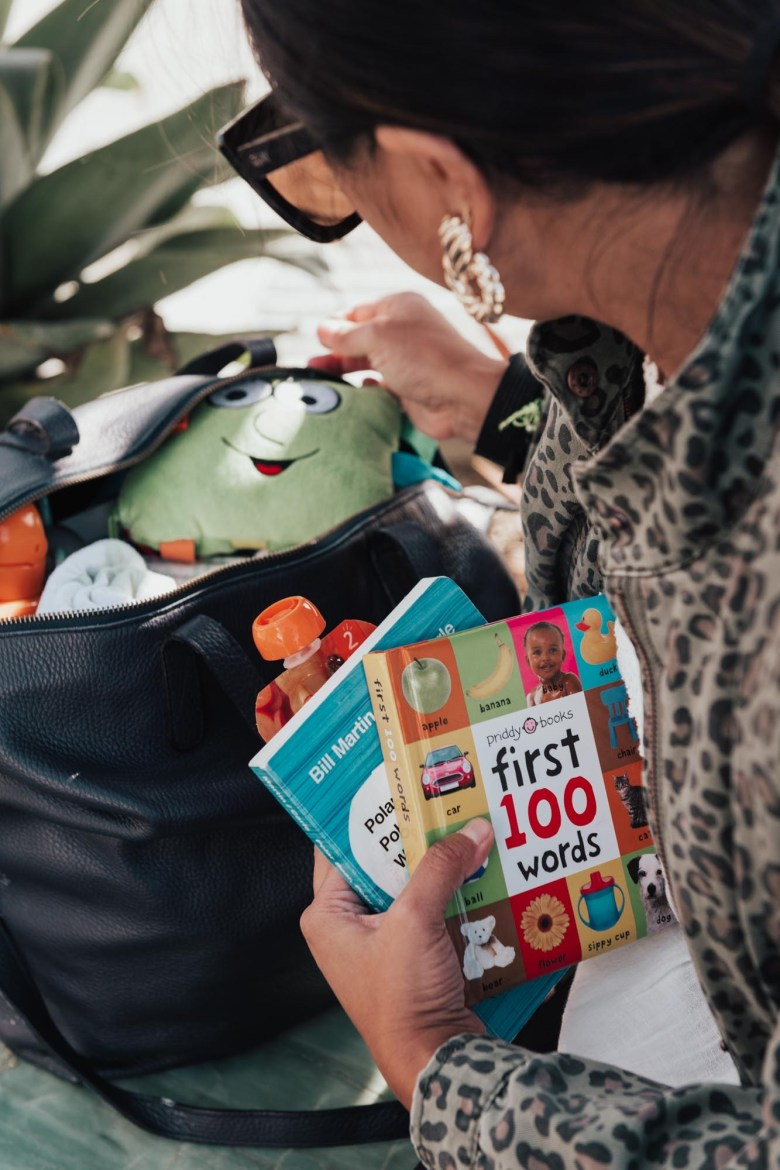 Best Diaper Bag Essentials for 2019 & 2020 by popular San Francisco lifestyle blog, Sylvie in the Sky: image of a woman looking in an opened diaper bag with books, wipes, diapers, and Happy Baby squeeze pouches.