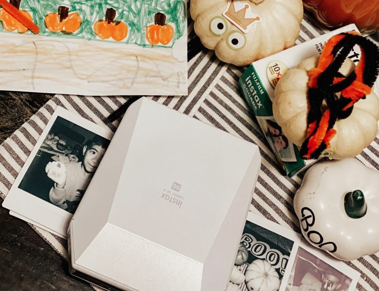 Easy Pumpkin Decorating Ideas for Toddlers & Kids by popular San Francisco lifestyle blog, Sylvie in the Sky: image of decorated mini pumpkins next to an Instax SP-3 SHARE Printer.