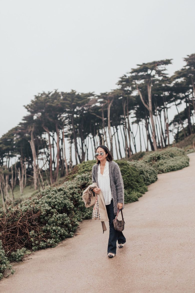 Women's Trench Coats and Outfit Inspiration by popular San Francisco fashion blog, Sylvie in the Sky: image of a woman standing outside at the beach and wearing a Nordstrom Burberry Kensington Long Trench Coat, NEXT SLIDEclick to zoom 1 / 4 SHARE RIVES MOHAIR CARDIGAN ON FACEBOOK ACNE STUDIOS Rives Mohair Cardigan, and holding a Mark and Graham DAKOTA HIDE TOTE.