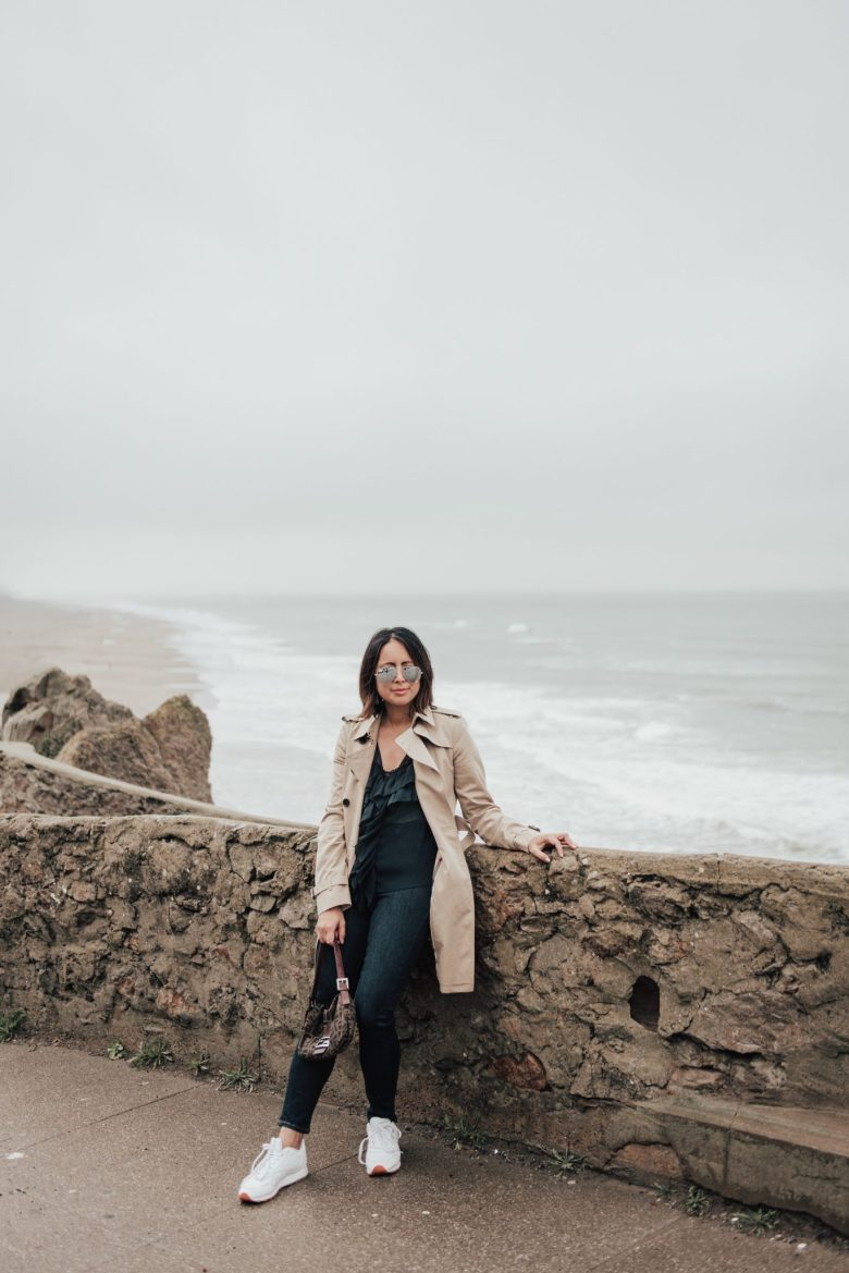 Women's Trench Coats and Outfit Inspiration by popular San Francisco fashion blog, Sylvie in the Sky: image of a woman outside and wearing a Burberry Kensington Long Trench Coat and Reebok Classic Leather Sneaker.
