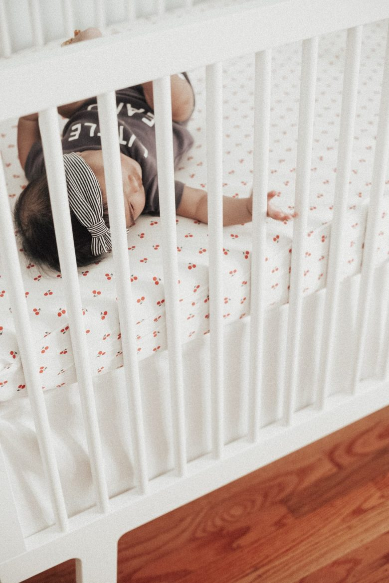 11 Best Gender Neutral Nursery Baby Products by popular San Francisco life and style blog, Sylvie in the Sky: image of a baby laying in a white crib.