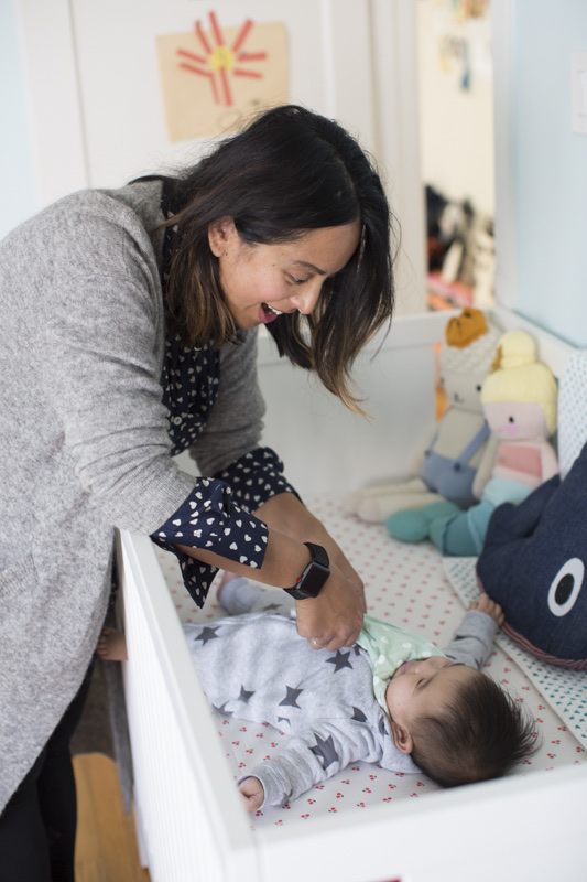 11 Best Gender Neutral Nursery Baby Products by popular San Francisco life and style blog, Sylvie in the Sky: image of a mom leaning over a crib railing and looking at her baby.