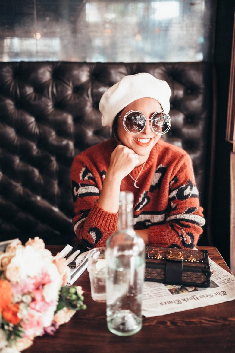 8 Smart Holiday Shopping Tips by popular San Francisco life and style blog, Sylvie in the Sky: image of a woman sitting in a restaurant and wearing a cream color beret, Cheetah print sweater, and round frame sunglasses.