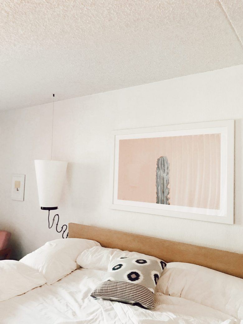How to Sleep Better by popular San Francisco lifestyle blog, Sylvie in the Sky: image of a bed with white linens and a image of a cactus with a pink background.
