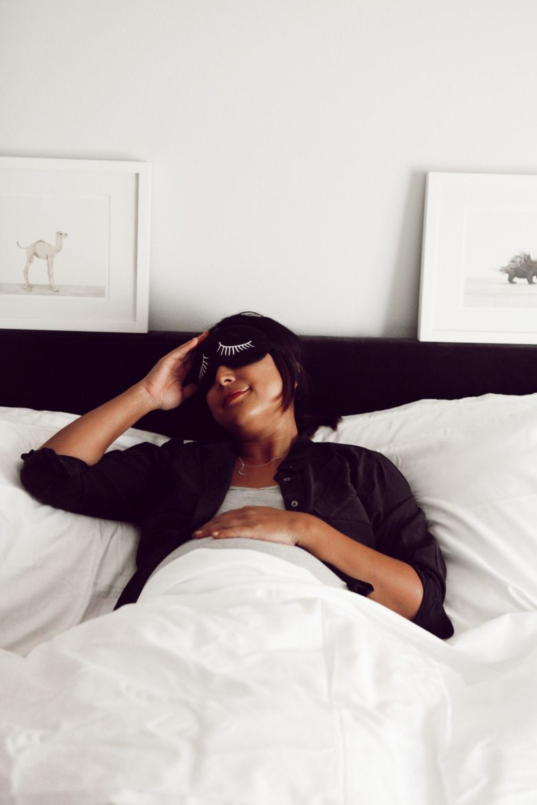 How to Sleep Better by popular San Francisco lifestyle blog, Sylvie in the Sky: image of a woman wearing with a black sleep mask and laying in a bed with white linens and a black headboard.