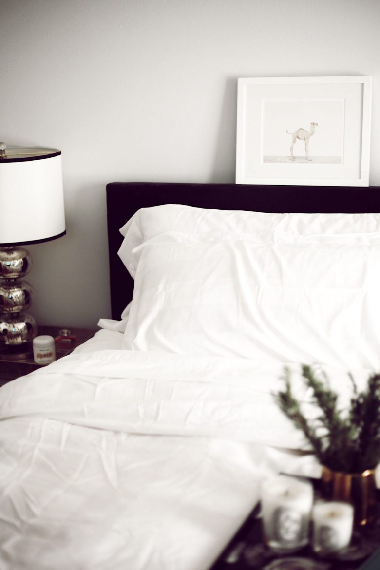 How to Sleep Better by popular San Francisco lifestyle blog, Sylvie in the Sky: image of a bed with white linens and a black headboard.