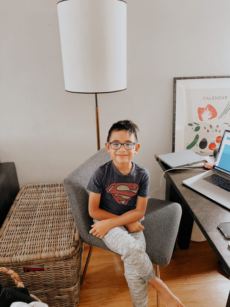 Blue Light Glasses by popular San Francisco motherhood blog, Sylvie in the Sky: image of a young boy sitting in a chair next to a open laptop and wearing a pair of blue light glasses.