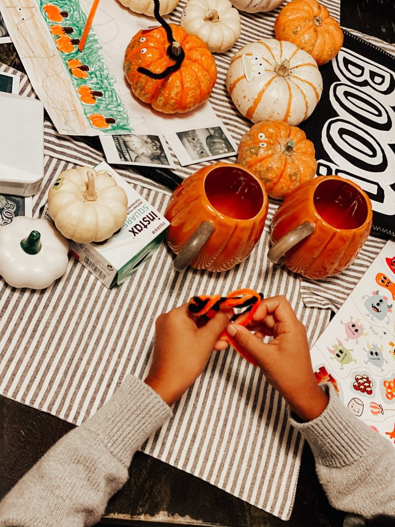 At Home Halloween by popular San Francisco motherhood blog, Sylvie in the Sky: image of pumpkin mugs, small pumpkins, and a child doing a craft with orange and black pipe cleaners.