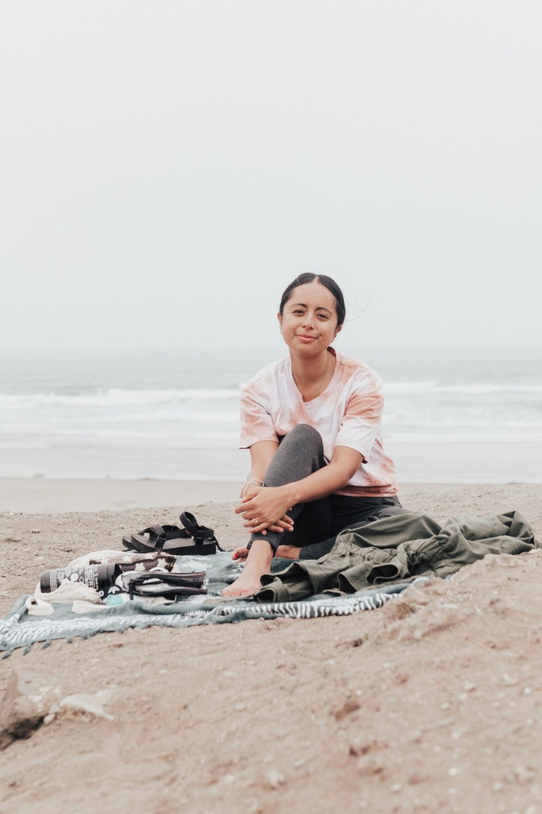 Breathwork Meditation by popular San Francisco lifestyle blog, Sylvie in the Sky: image of a woman wearing a tie dye shirt and sitting on a blanket at the beach.