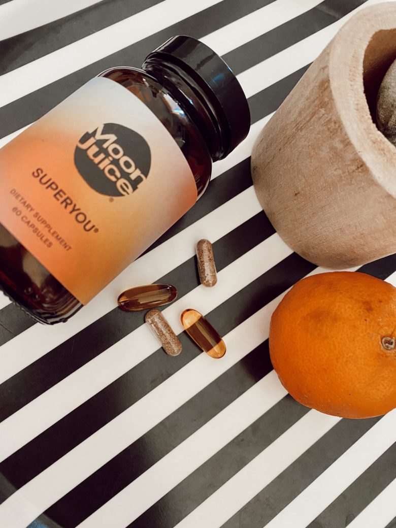 Wellness Supplements by popular San Francisco lifestyle blog, Sylvie in Sky: image of some Moon Juice and some supplements next to an orange.