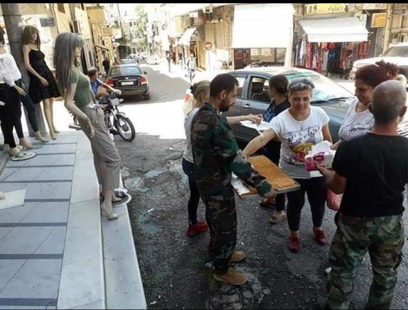 Syrians distributing sweets on the streets in Suqaylabiyah