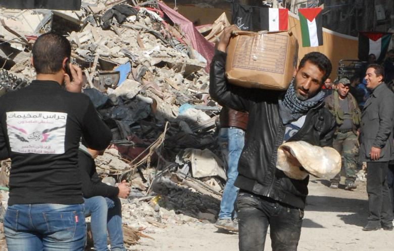 A handout picture released by the official Syrian Arab News Agency (SANA) on January 30, 2014 shows residents of Syria's besieged Yarmuk Palestinian refugee camp, south of Damascus, receiving food parcels from the UN Palestinian refugee agency (UNRWA). (Photo: AFP/SANA)