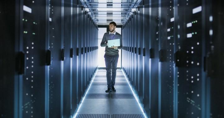 IT Technician Works on Laptop in Big Data Center full of Rack Servers.