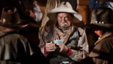 13791189 - bluffing card player in old american west saloon. hands in focus.