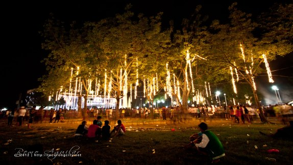 People sitting under a lighted tree