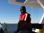 Karen in cold weather clothing at the helm
