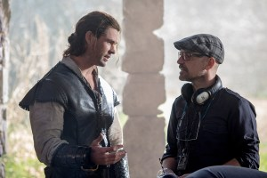 """(L to R) CHRIS HEMSWORTH as Eric the Huntsman and director CEDRIC NICOLAS-TROYAN on the set of """"The Huntsman: Winter's War,"""" the story that came before Snow White. Hemsworth and Oscar® winner Charlize Theron return to their roles from """"Snow White and the Huntsman,"""" joined by Emily Blunt and Jessica Chastain."""