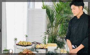 料理に目をやるシェフの写真