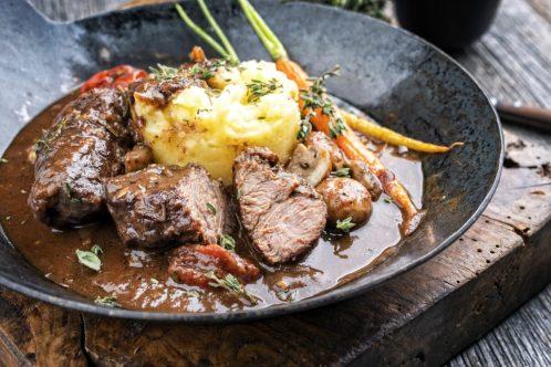 鉄フライパンに盛られた牛肉の赤ワイン煮込み